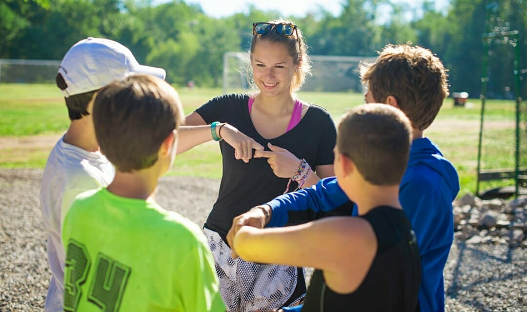 camp counselor talking to group of boys