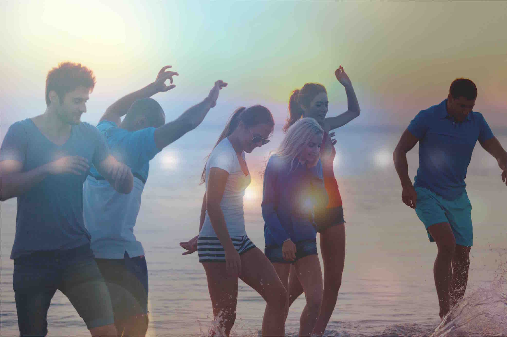 group of friends dancing at the beach