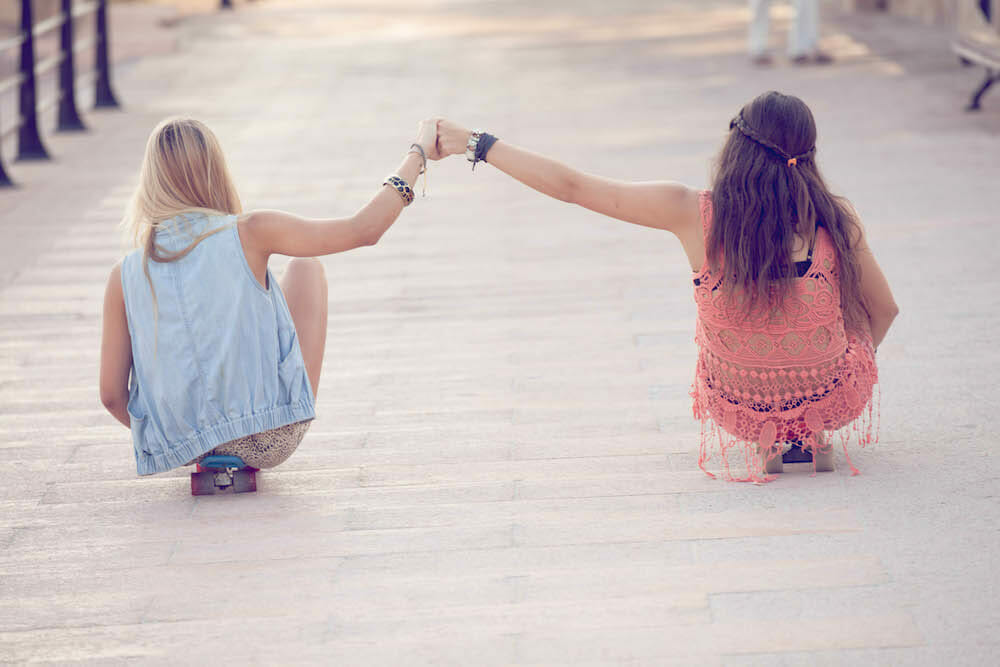 two girl friends holding hands