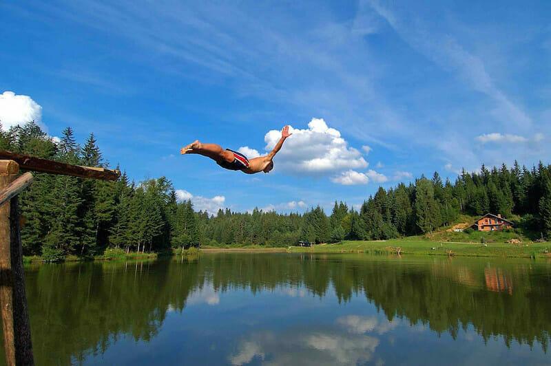 boy diving into lake