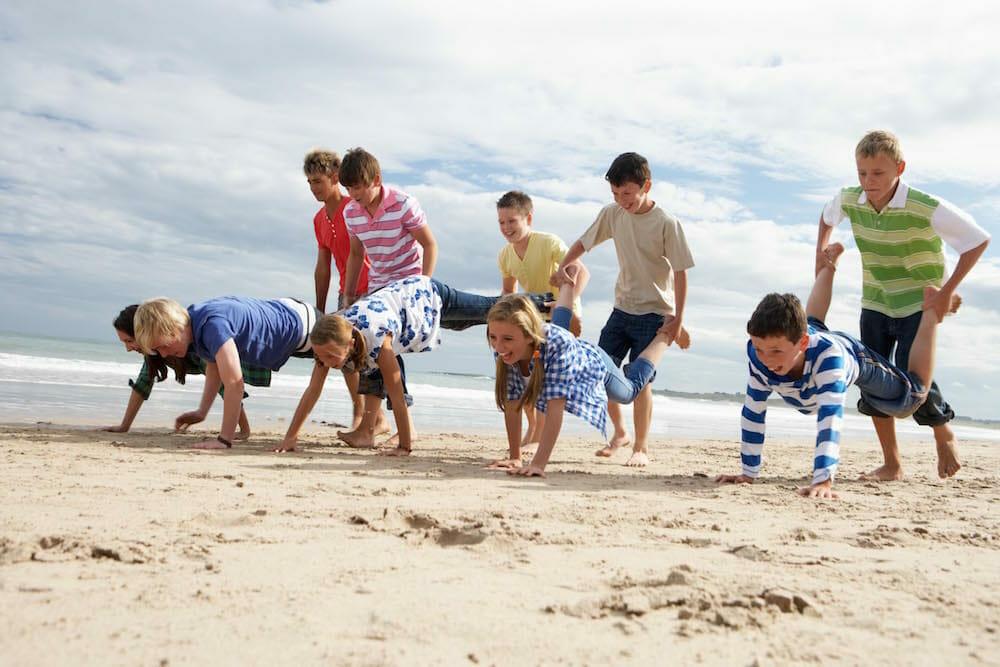 group of kids wheel barrowing on the beach