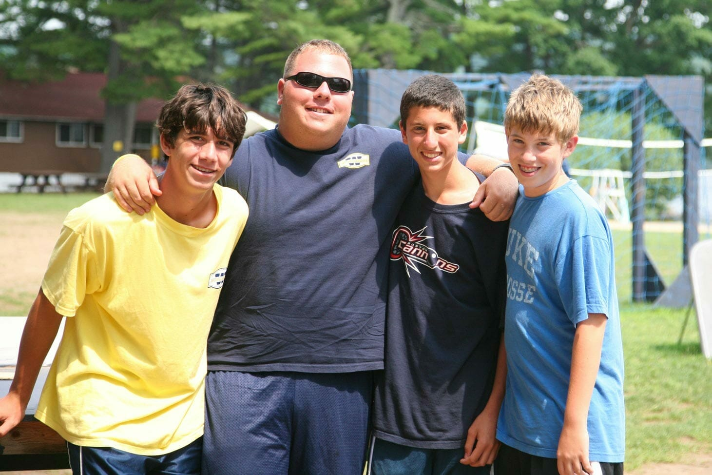 Boys embrace their counselor at American summer camp