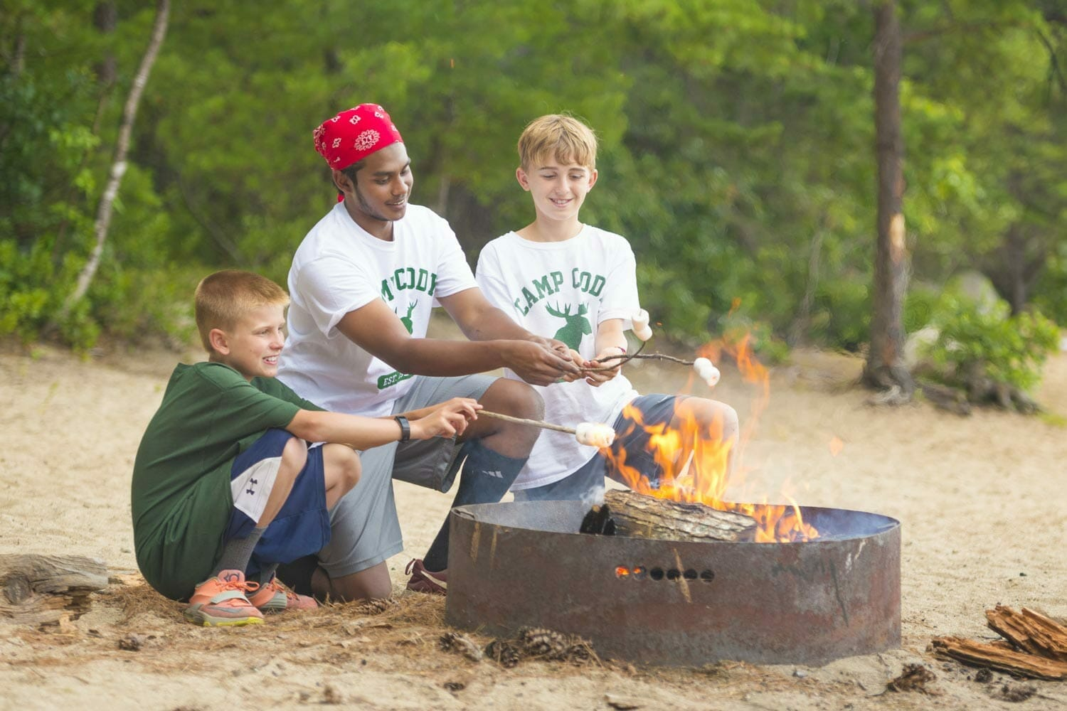 Boys building a campfire at summer camp in America