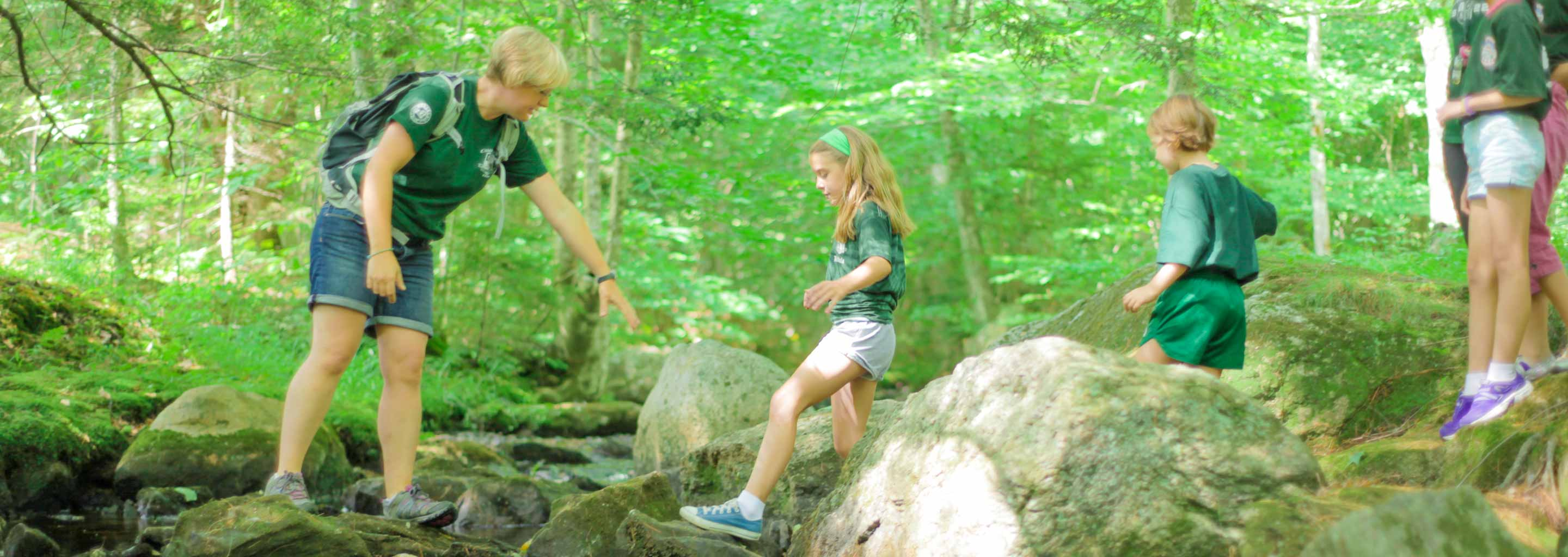 Counselor leads girl at camp