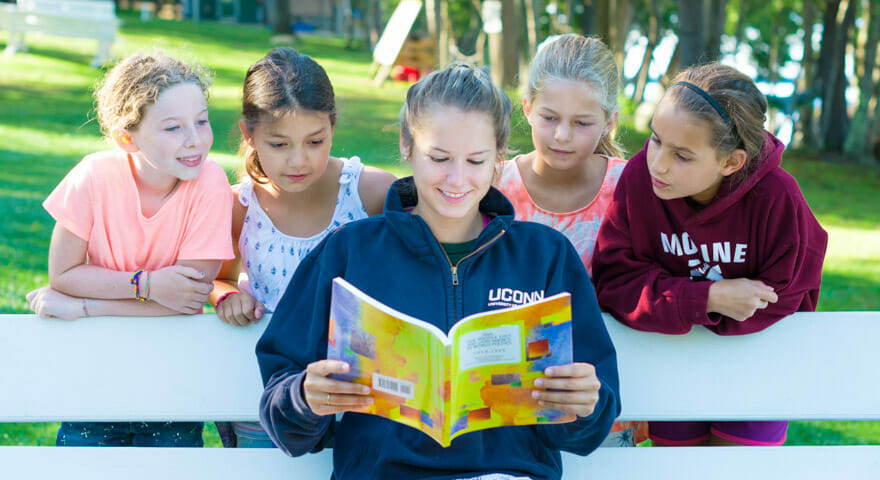 Female counselor reading to campers