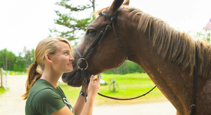 Female support staff with horse at camp