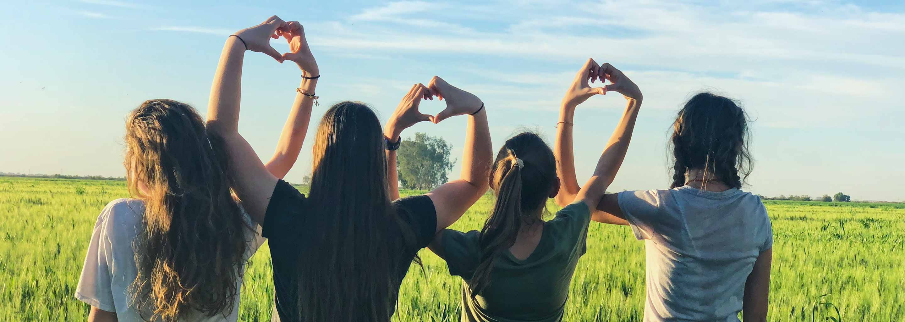 Girl friends with heart hands pose