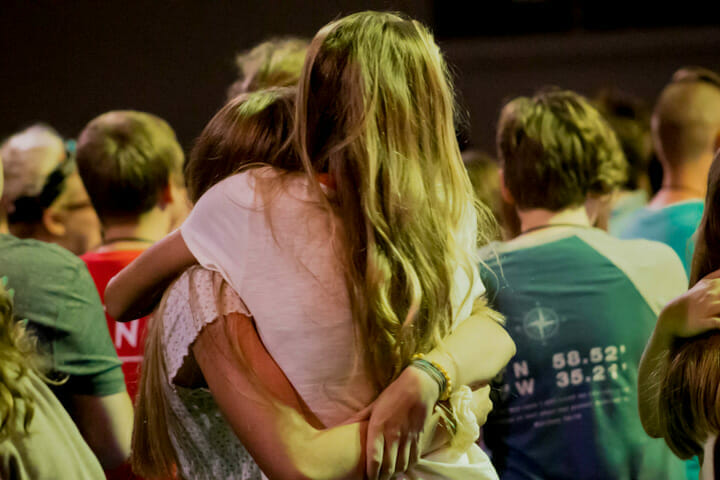 Girls hug as they depart summer camp