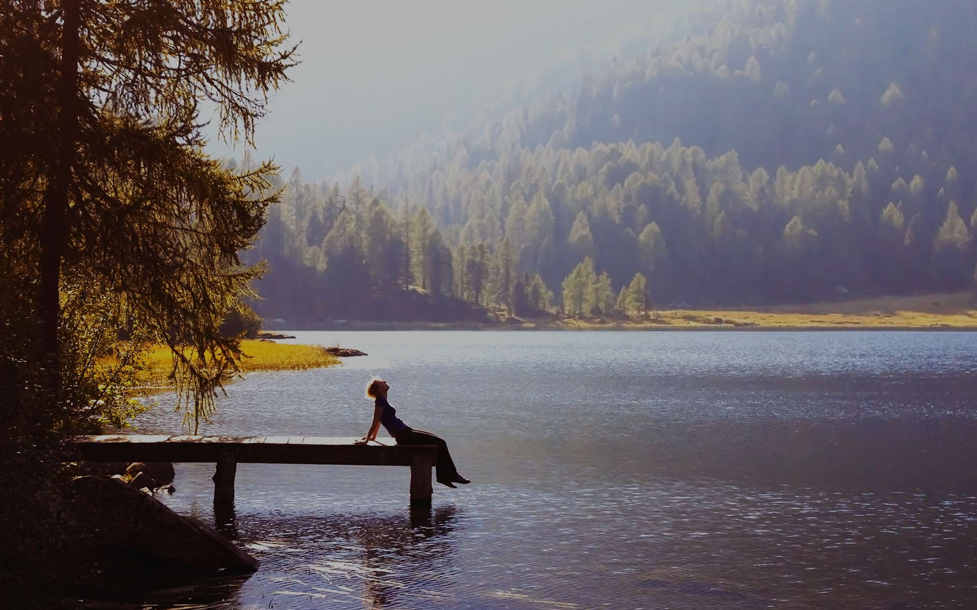 woman sitting on edge of a lake doc