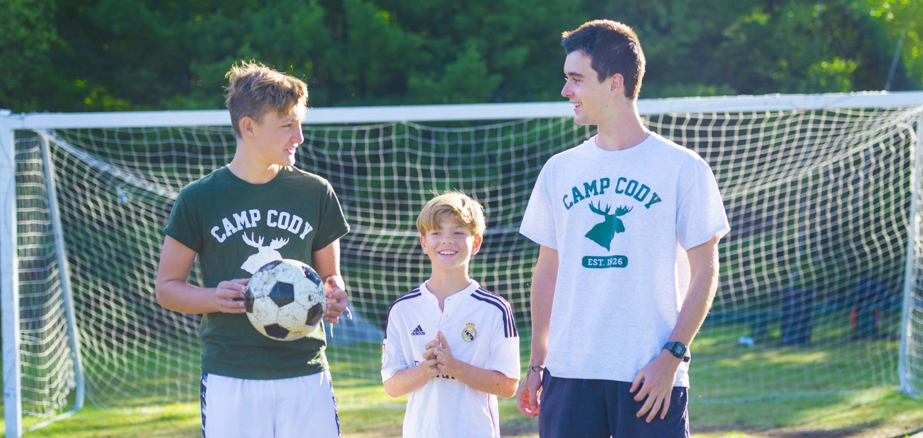 Soccer coaches and camper at summer camp