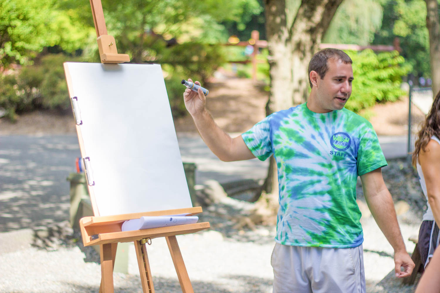 Male counselor teaches art class at camp