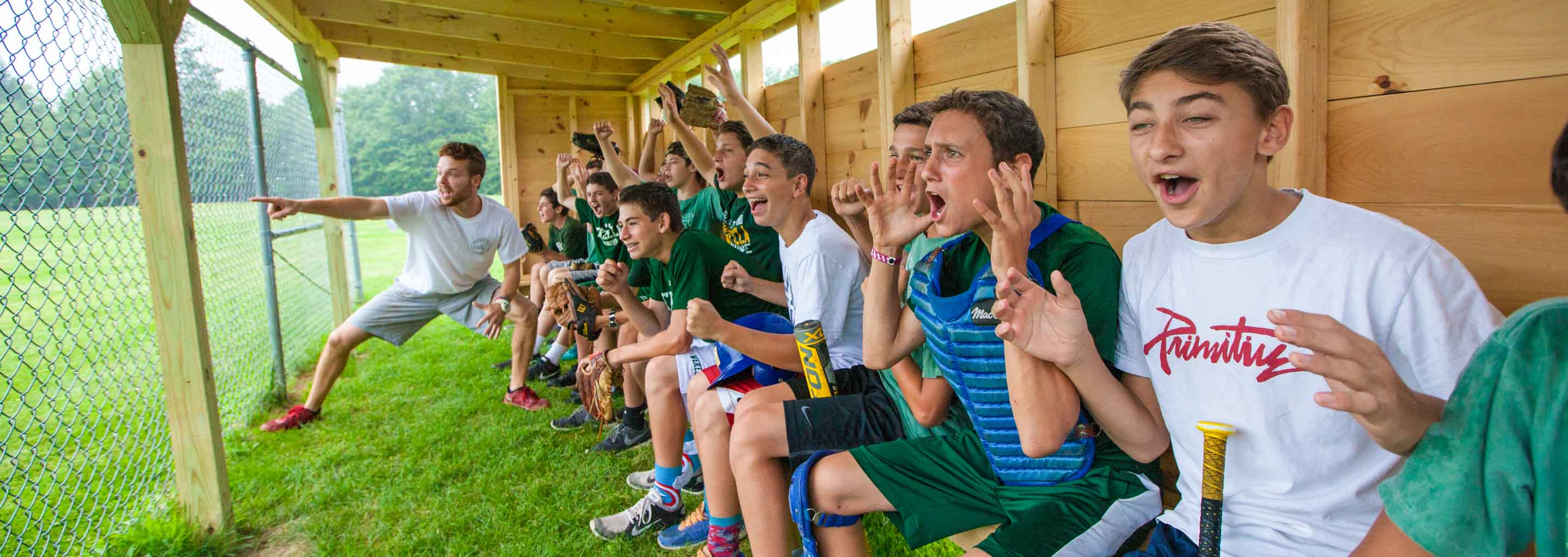 Boys goof around in USA dugout at camp