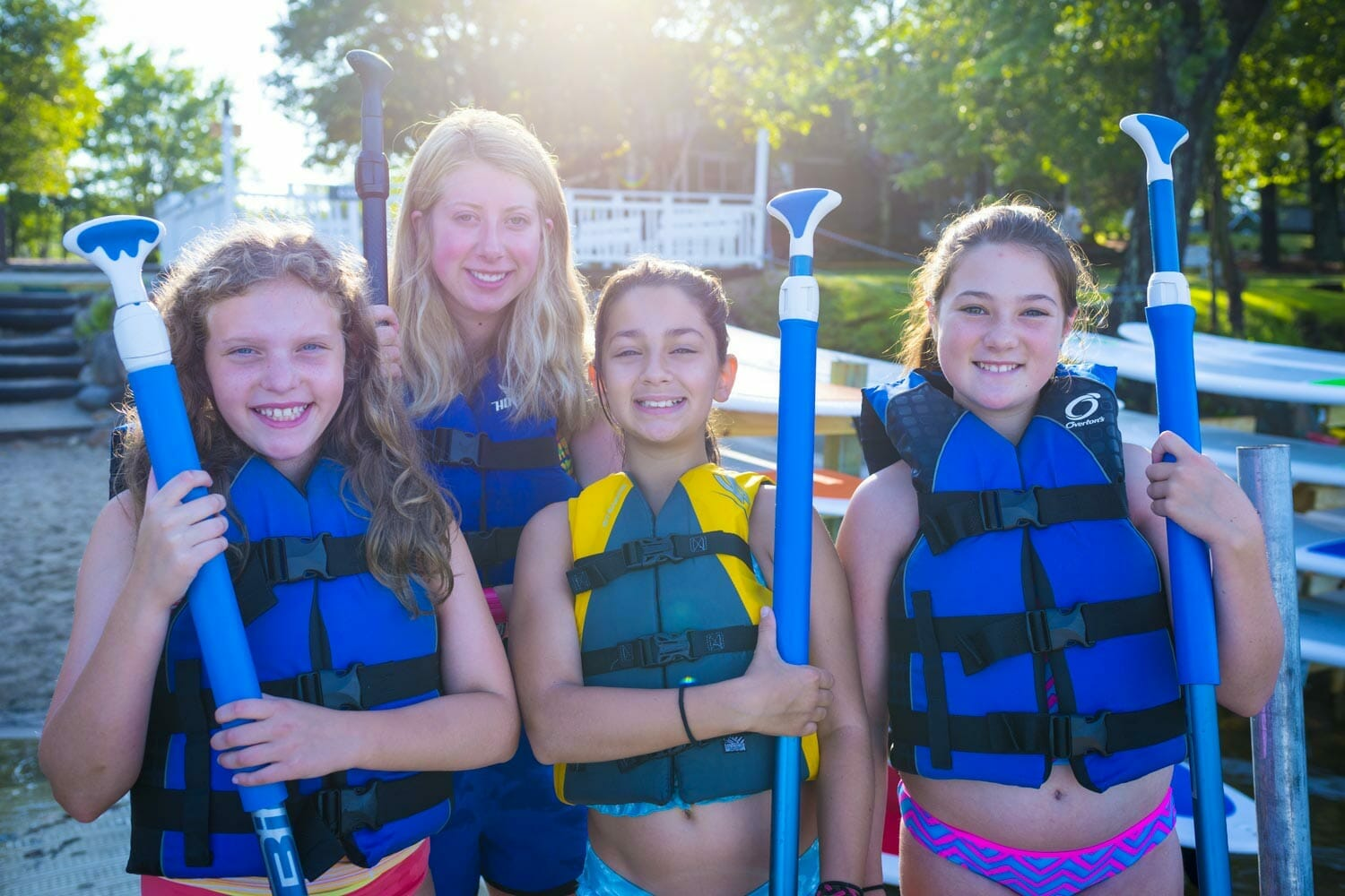 Girls and their counselor prepare to paddle at summer camp