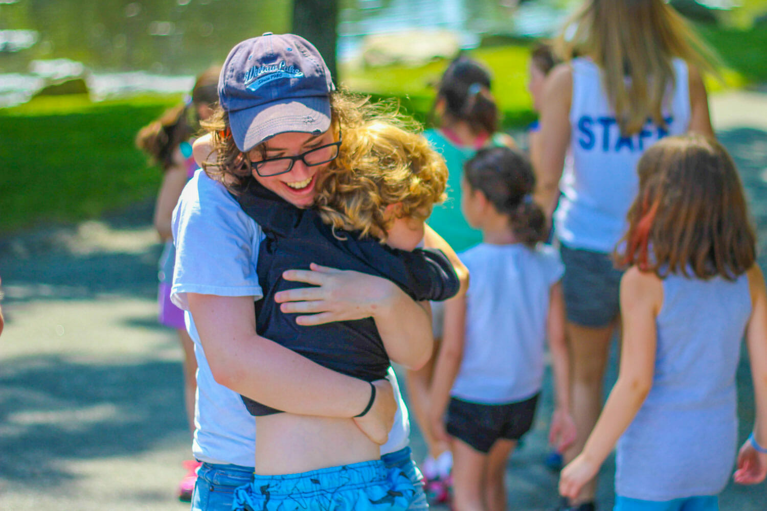 Counselor Hugs a Camper at Summer Camp