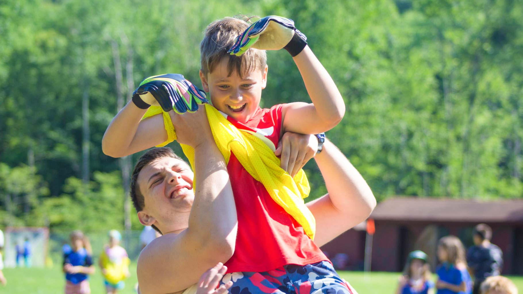 Boy and counselor celebrate a goal at summer camp