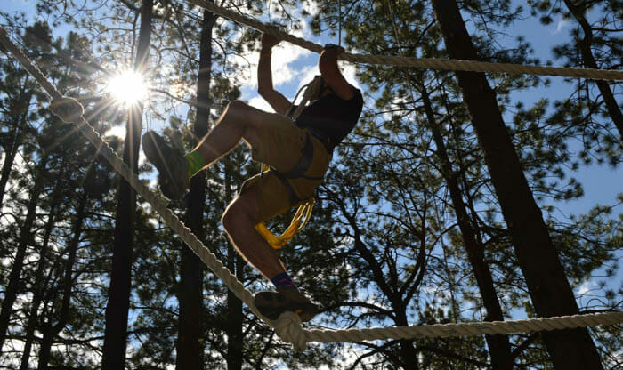 consoler walking across ropes course with full harness