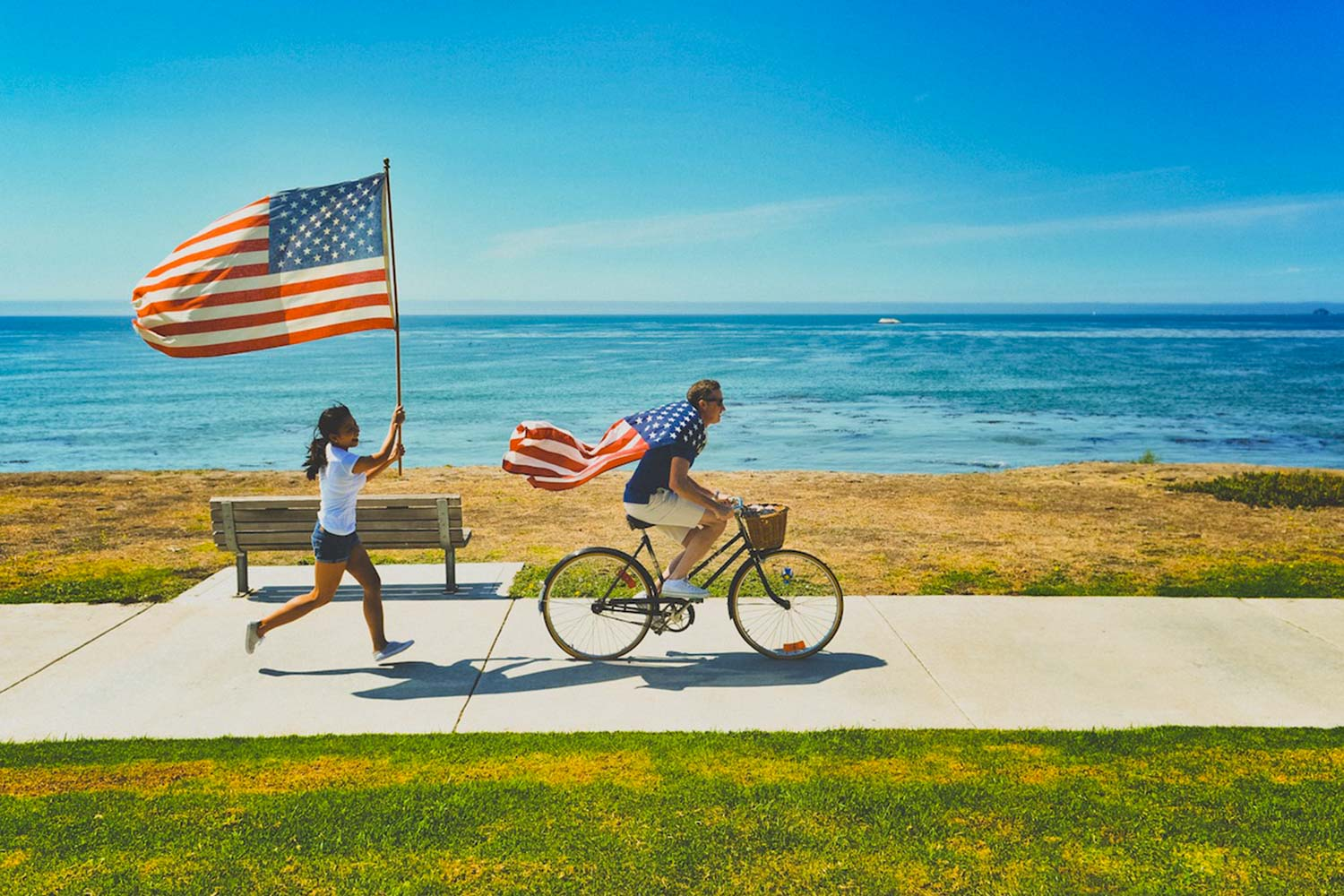 Girl chases man on bike with American flag