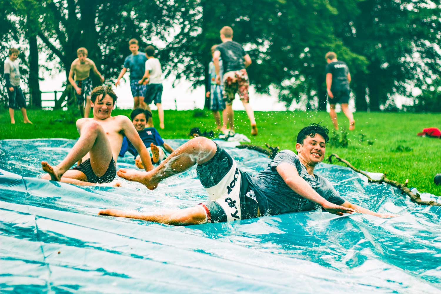 Boys slip and slide at summer camp in USA